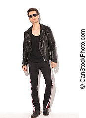 arrogant young fashion man in leather jacket and sunglasses posing