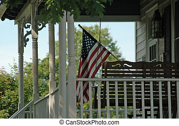 American Patriotism - Flag on front porch of old farm house