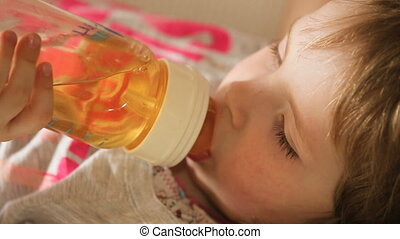 Baby drinking juice form bottle. - The young girl lies on a...