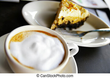 cup of frothy coffee and cake, closeup
