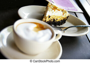 Cup of  frothy coffee and cake, cake is sharp