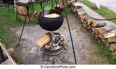 Cooking In A Hike In The Cauldron Hanging Over fire -...