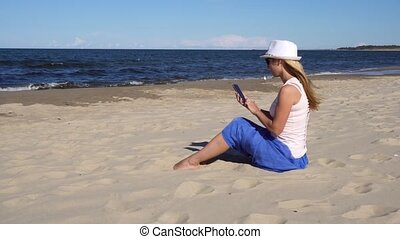 woman making photo of her kids on the sea beach - young...