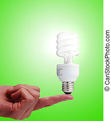 Compact fluorescent bulb on a finger, on green