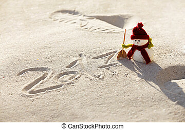 Toy snowman on the sand and figures 2017