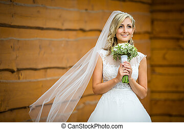 Gorgeous bride on her wedding day  holding her lovely bouquet