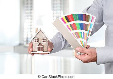 Hands with house and swatches, interior design concept