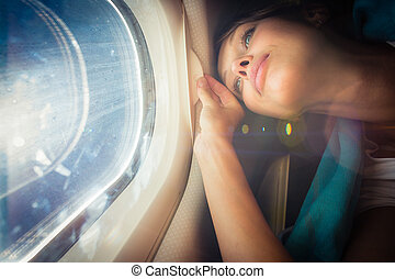 Happy, female airplane passanger enjoying the view from the...