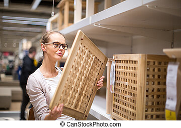 Pretty, young woman choosing the right furniture for her...