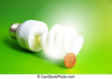 light bulb with a penny, energy costs, on green