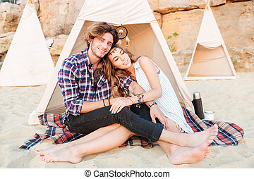Couple relaxing and hugging in wigwam on the beach - in...