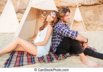 Couple sitting and resting near wigwam on the beach - in...