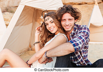 Couple sitting and hugging near wigwam on the beach - in...