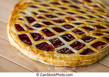 Pie on wooden surface. Dough with berries. Freshly cooked...