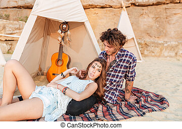 Relaxed young couple resting near wigwam on beach - in...