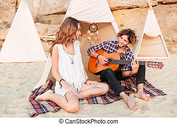 Couple relaxing and playing guitar in wigwam on the beach -...