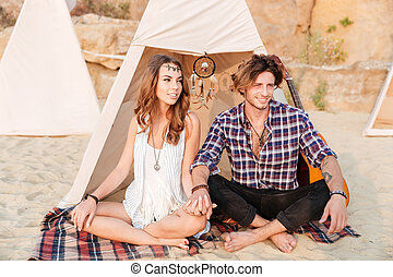Couple sitting with legs crossed at the beach near tent -...