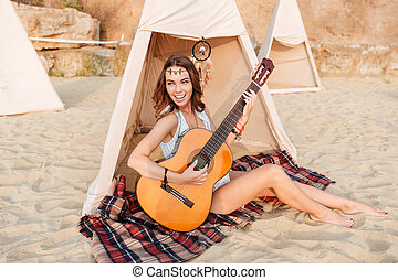Happy hippie girl playing guitar while sitting at the tent