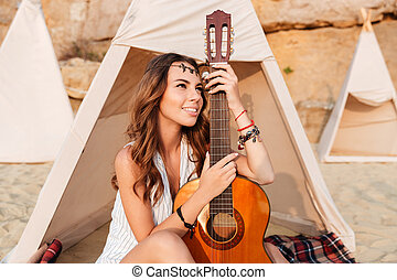 Happy woman sitting and holding guitar in wigwam on beach -...