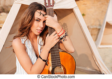 Close up portrait of a beautiful hippie girl with guitar -...