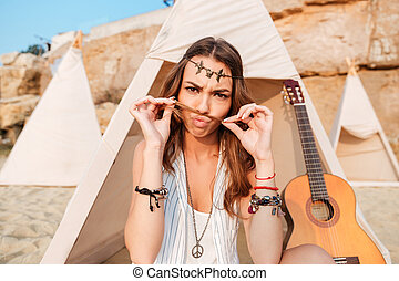 Amusing woman making funny face in wigwam on the beach - in...