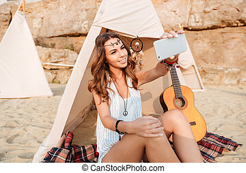 Woman taking selfie with smartphone in wigwam on the beach -...