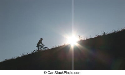 camera following female mountainbiker up hill at sunset