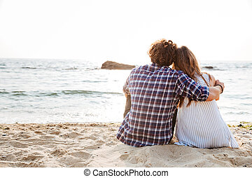 Back view of couple sitting and relaxing on the beach