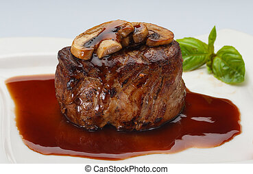 Steak with sauce on a white plate