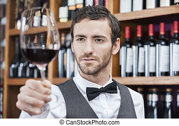 Bartender Examining Red Wine In Glass At Shop - Young...