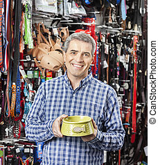 Happy Customer Holding Food Bowl At Pet Store - Portrait of...