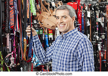 Customer Buying Pet Leash At Store - Portrait of happy male...