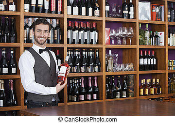 Male Bartender Holding Red Wine Bottle In Shop - Portrait of...