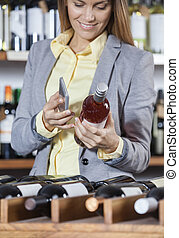 Woman Scanning Bar Code On Wine Bottle With Mobile Phone -...