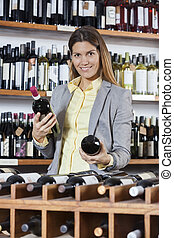 Mid Adult Woman Choosing Between Wine Bottles - Portrait of...