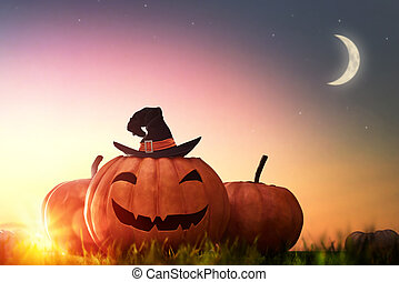 pumpkin and hat witch on sunset - Happy halloween! Head...