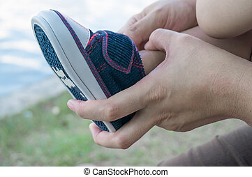 Mother Help Child Put on Shoe - Hands of Mother Helping Her...