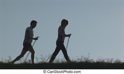 two nordic walkers close - two nordic walkers walking...