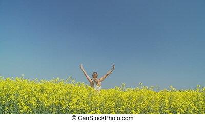 happy woman turning in rape field, wide - happy woman...