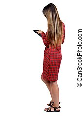 back view of standing young beautiful woman and using a...