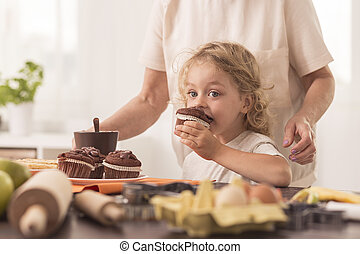 Chocolate is my best friend - Beautiful small girl tasting a...