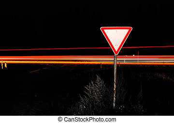 Road sign give way Road sign at night on the background...