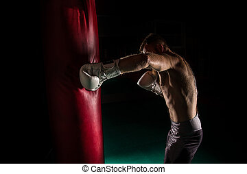 Muscular hipster fighter giving a forceful kick during a...