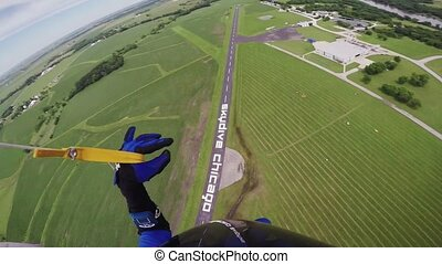 Professional skydiver parachuting in blue sky above green fields. Landscape