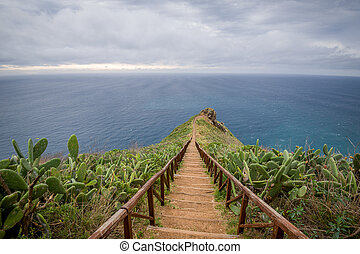 Wooden steps path from Cristo Rei statue to the ocean cape....