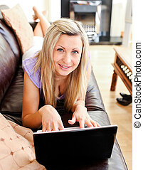 Nice woman lies on sofa and working with a laptop