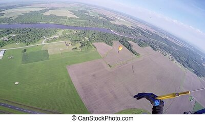 Professional skydiver parachuting in blue sky over green fields. Landscape.