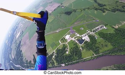 Professional skydiver parachuting in blue sky above green flatland and river.