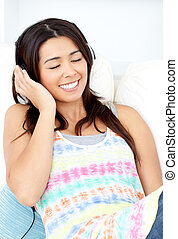 Radiant young woman sitting on sofa and listening music