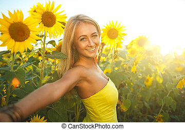 Beautiful woman with sunflowers in the sunset